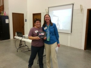 Lavinia presents a plaque from Hooked on Hope to Maura, co-captain of The Adventurous Woman, thanking them for their support of the Hooked on Hope Fishing Tournament.