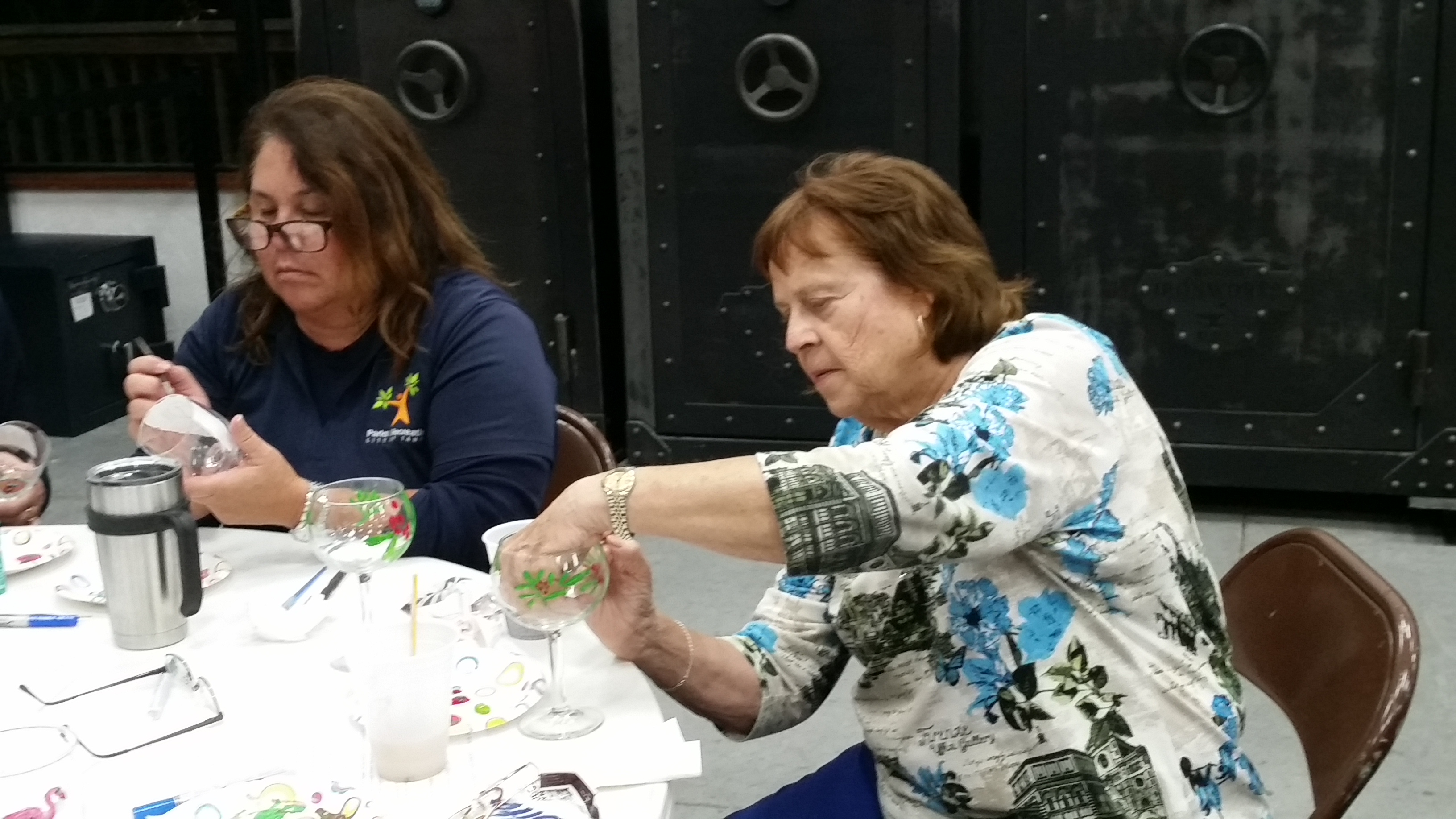 Loretta and Kay painting Christmas glasses.