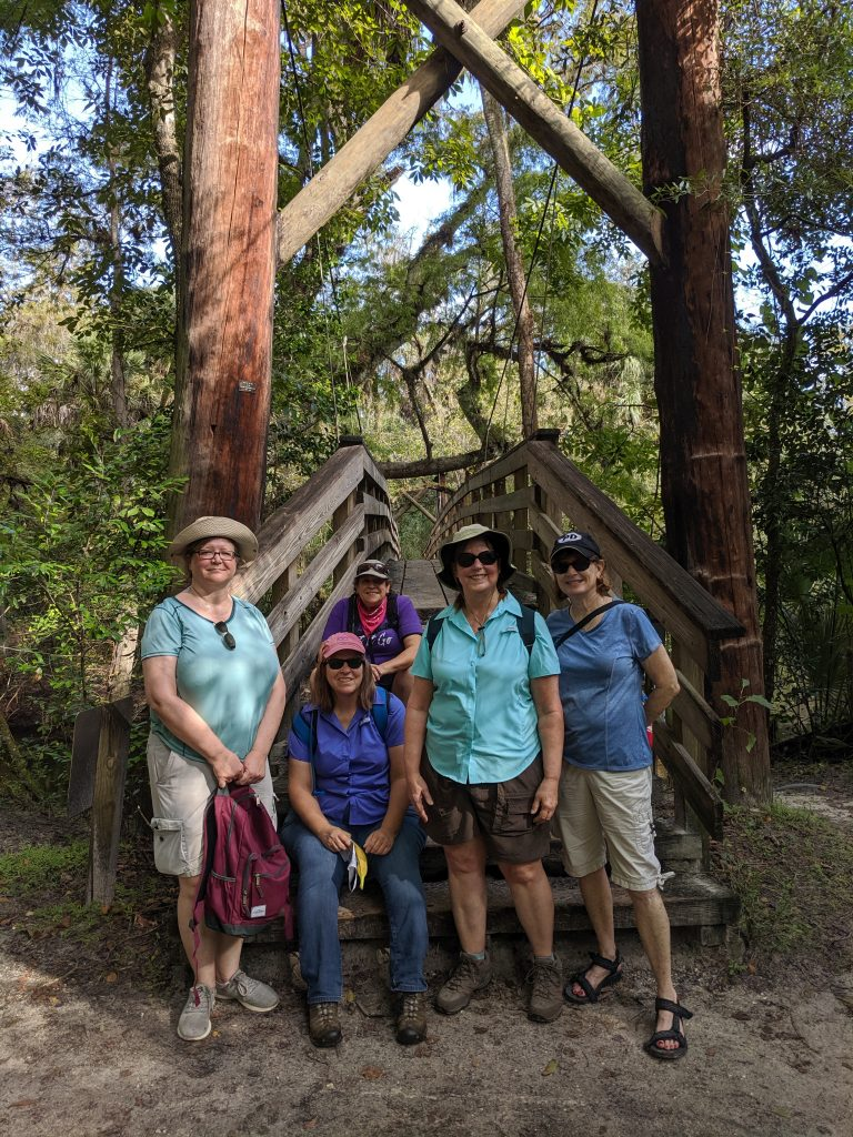 Five women from the Adventurous Woman's outdoor group pose for a picture at the entrance to the suspension bridge crossing the river at Hillsborough River State Park