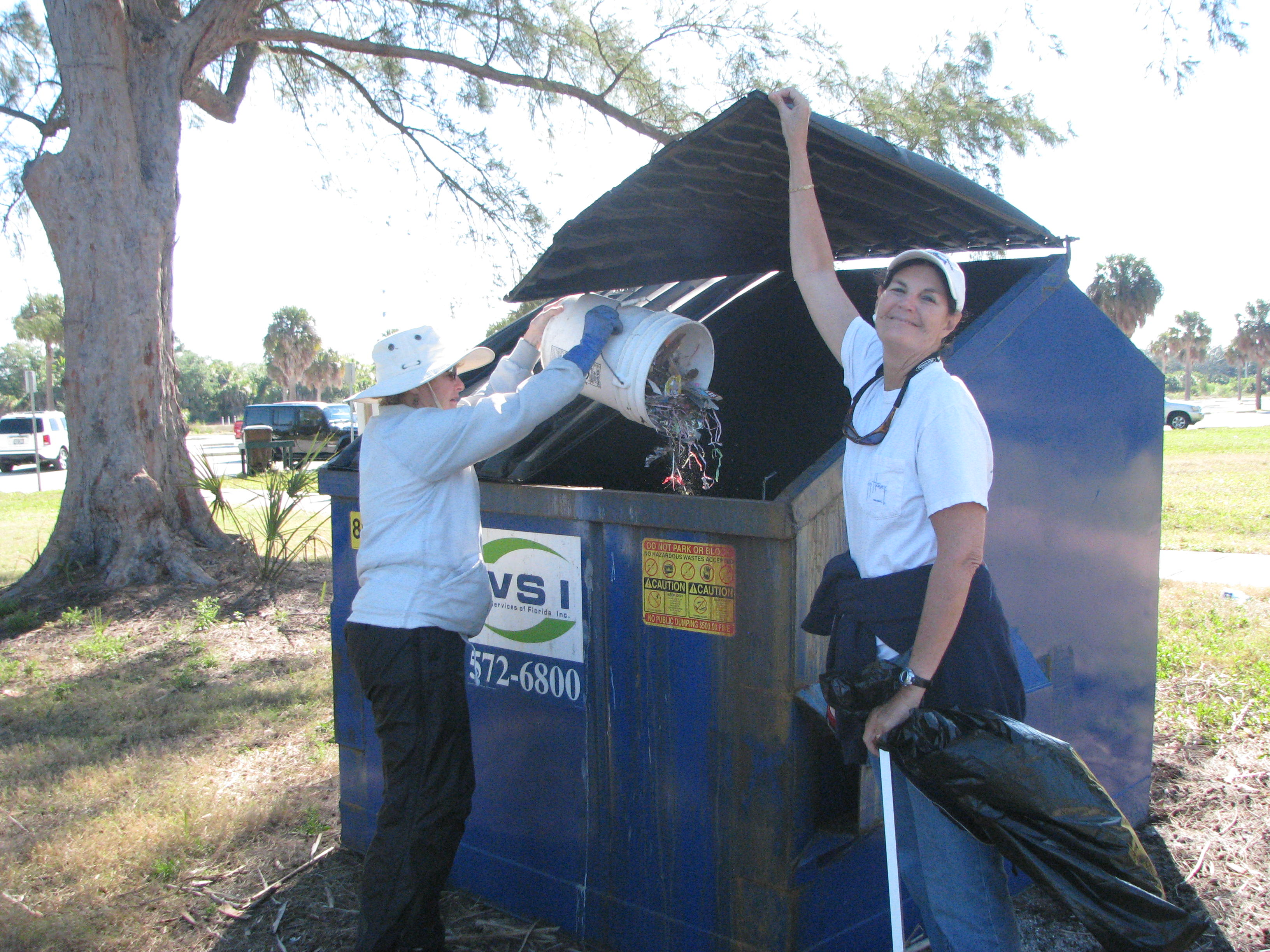 Emptying a bucket of trash into the dumpster