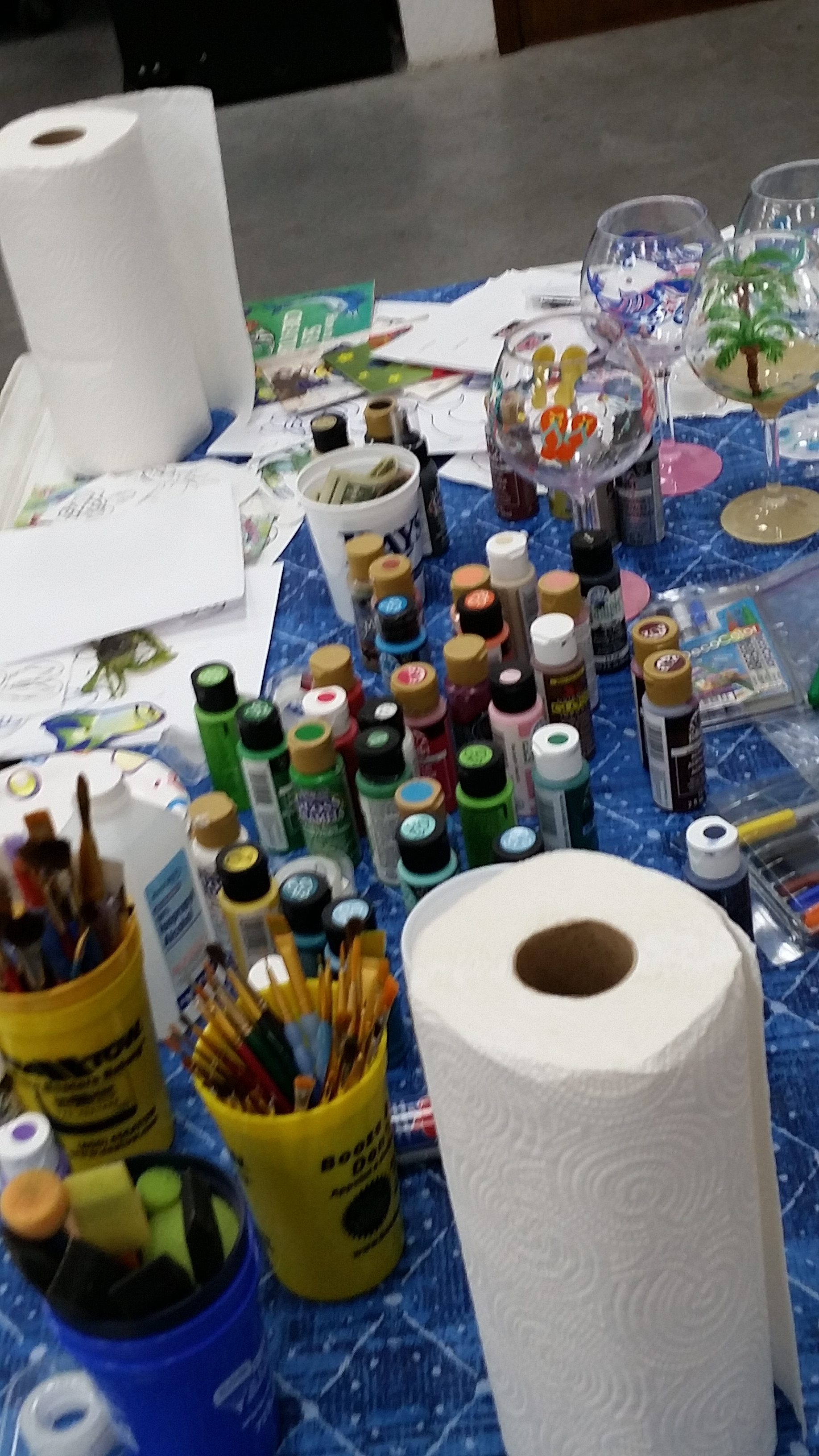 Paint, pencils, paper towels and other supplies needed for painting glasses.